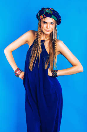 blue overall: sexy blond woman in blue turban in overall on blue background