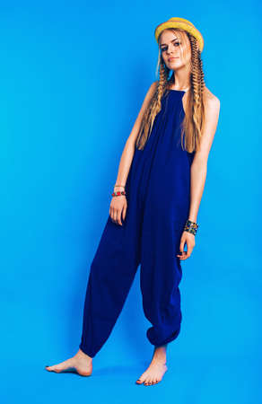 blue overall: cute blond woman in blue overall and yellow hat on blue background Stock Photo