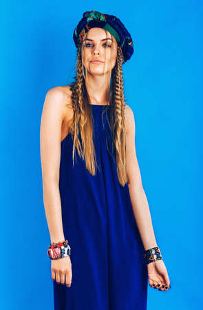 blue overall: sexy blond woman in ultramarine turban and overall on blue background Stock Photo
