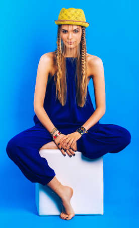 blue overall: blond woman in blue overall and hat sitting on chair on blue background
