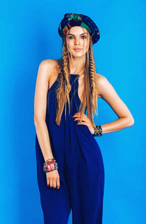 ultramarine blue: attractive woman in ultramarine turban and overall on blue background