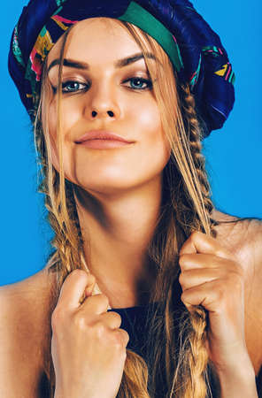 plaits: beautiful blond woman with plaits in turban on blue background