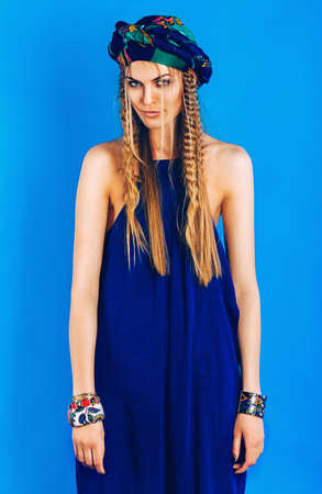 blue overall: sexy blond woman in ultramarine turban in overall on blue background