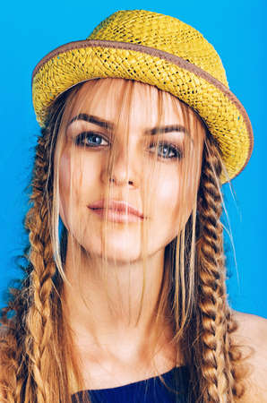 ultramarine blue: portrait of blond woman in straw hat with plaits on blue background
