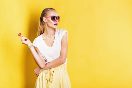 fashion sunglasses: attractive woman in white top with lollipop in hand on yellow background Stock Photo