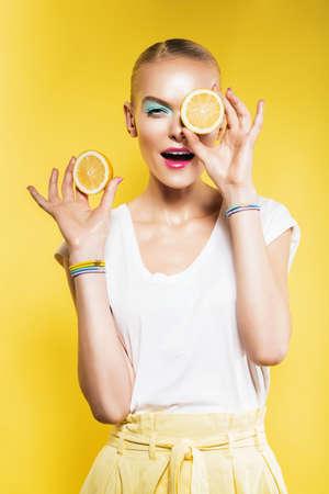 lemon: hermosa mujer con una rodaja de lim�n en el ojo en fondo amarillo Foto de archivo