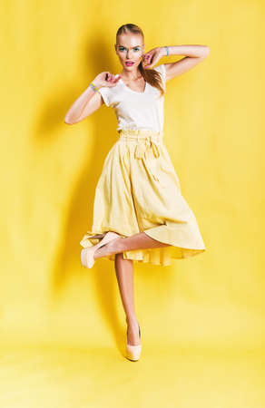 cute blond woman in yellow skirt on yellow background