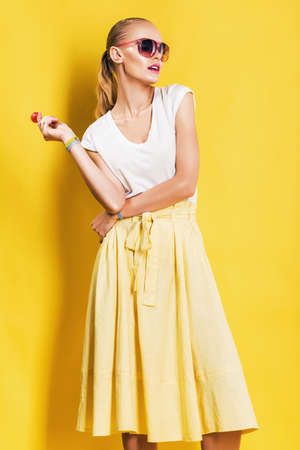 hot woman in yellow skirt with lollipop on yellow background