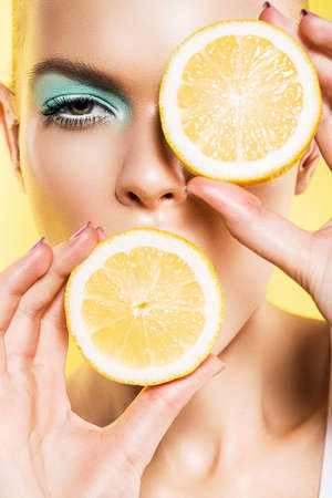 portrait of woman with slices of lemon near face on yellow background
