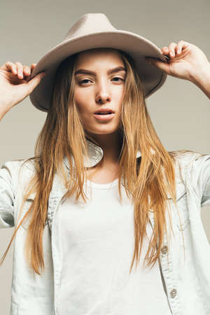 white t shirt: beautiful woman in white t shirt and hat in studio Stock Photo
