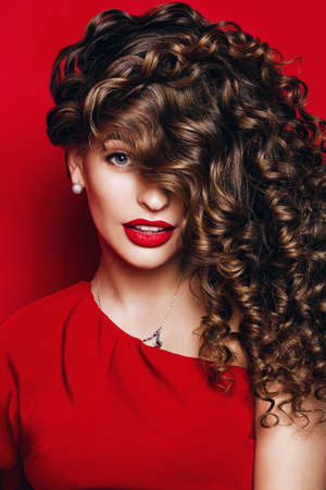 cute woman with red lips in red dress with curls on red background