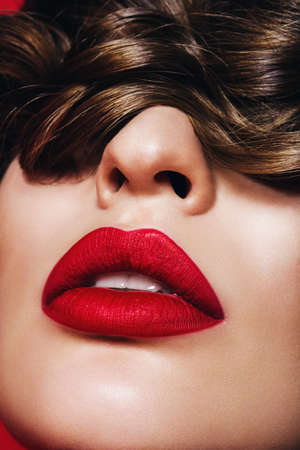 close up portrait of woman with passionate lips with hair on eyes