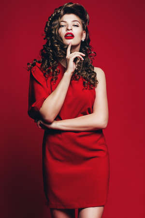 hot woman in red dress with curls on red background Stock Photo
