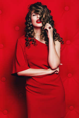 hot woman with curls in red dress on red background Stock Photo