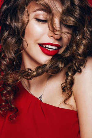 dynamic happy woman with flying curly hair and red lips