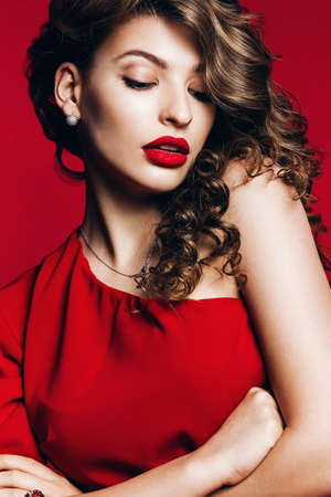 hot woman in red dress with red lips on red background Stock Photo