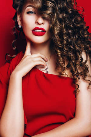 woman with curls on eye with red lips on red background