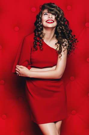 smiling woman in red dress with curls on red background