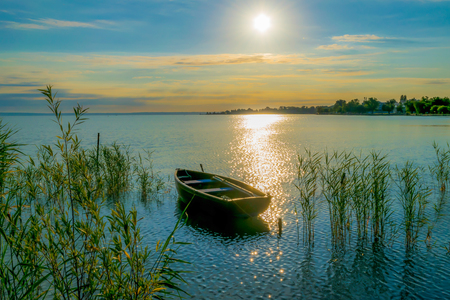 Rowing boat on lake at sunset.  Small wooden rowing boat on a calm lake at sunset. Stock Photo