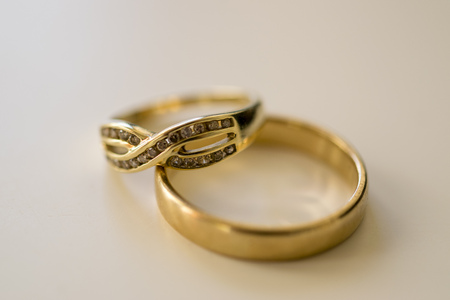 Gold rings macro. Close up photo of a male wedding ring and a female eternity ring.