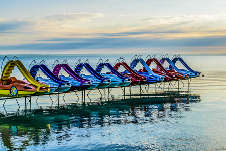 Colorful paddle bikes on calm summer lake. Row of vivid pedal bikes, summer morning, Lake Balaton, Hungary. Banco de Imagens