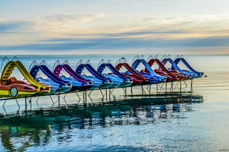 Kleurrijke peddelfietsen op kalm de zomermeer. Rij van levendige pedaalfietsen, de zomerochtend, Meer Balaton, Hongarije. Stockfoto