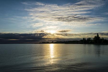 Beautiful sunrise over the lake. The rising sun shines through dramatic clouds, silhouette of trees on the shore of Lake Balaton, Hungary. Stock Photo