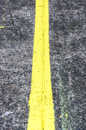 Top view of road with yellow line in middle, vertical. High angle view of gray asphalt road with a yellow line.
