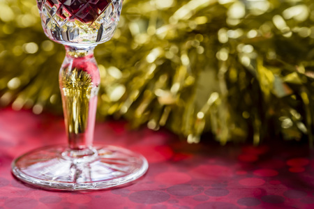 Glass of red wine detail, gold and red reflections on crystal. Christmas table closeup, gold tinsel decoration in background, side view.