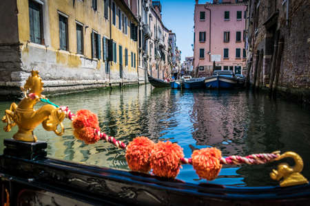 Canals and historic buildings of Venice, Italy, photo taken from gondola. Narrow canals, old houses, reflection on water on a summer day in Venice, Italy. Stock Photo