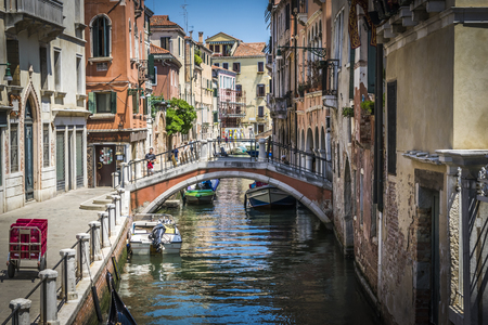 Canals and historic buildings of Venice, Italy. Narrow canals, old houses, reflection on water on a summer day in Venice, Italy.