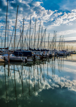 Calm lake, harbor and pier at sunrise. Harbor with sailboats and pier at dawn with dramatic clouds reflected in water, Lake Balaton, Hungary.