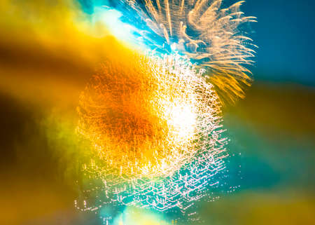 Abstract colorful fireworks on blue sky. Splashes of yellow, orange pattern, blue background.