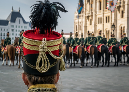 Hussar traditional military hat closeup. Background with the hussar cavalry on horses in front of the Parliament House during the 15 March military parade in Budapest, Hungary. Hungarian National Holiday.
