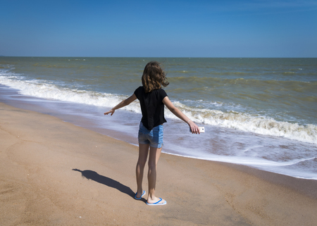 Girl stands at shore of ocean with open arms, facing water in Phuket, Thailand. Freedom, holiday concept. Teenage girl from back at sea beach, ocean waves, enjoys the wind.