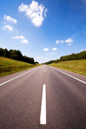 De geasfalteerde weg naar de zomer van het jaar. aan de randen van de weg op een hoogte gras en bomen (hout) groeit Stockfoto - 42484433