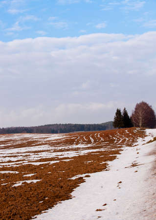 the plowed agricultural field during thaw. Winter.