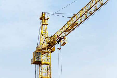 constitutive: photographed close-up of a yellow construction crane. against the sky