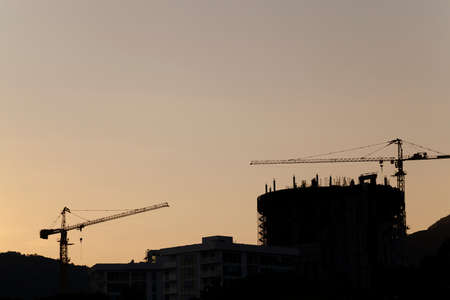 heave: the photograph shows two construction cranes in housing starts. Sunset. In the background mountains. Stock Photo