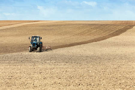 mechanization: a tractor plowing a field located in the land during planting.