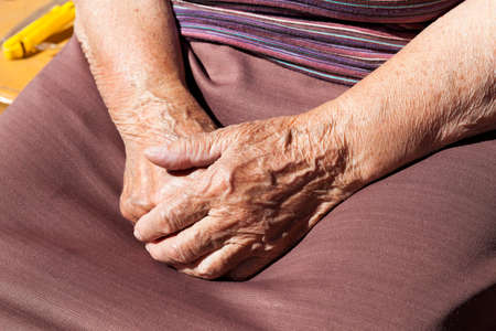 petticoat: photographed closeup of an old woman. hands folded together Stock Photo