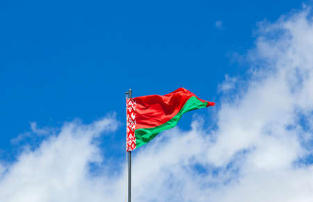 old flag: photographed closeup of the flag of Belarus. blue sky. ragged old flag Stock Photo
