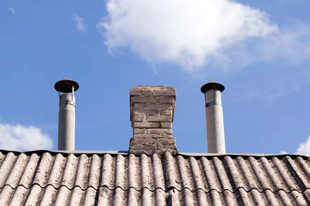 stove pipe: photographed close-up of part of the roof of a private building located on it with pipes for heating Stock Photo