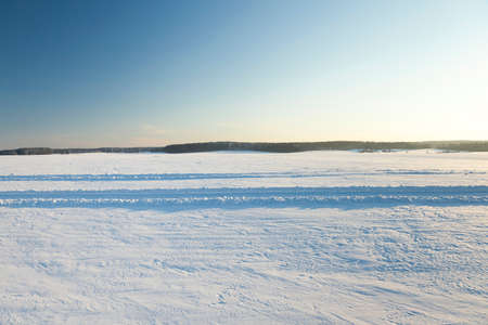 sheeted: an agricultural field in a winter season. the field is covered with snow after snowfall