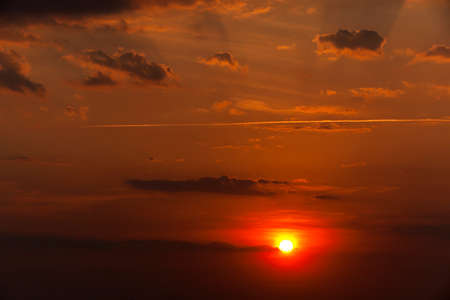 reveille: photographed a bright disk of the sun in the sky during sunset Stock Photo