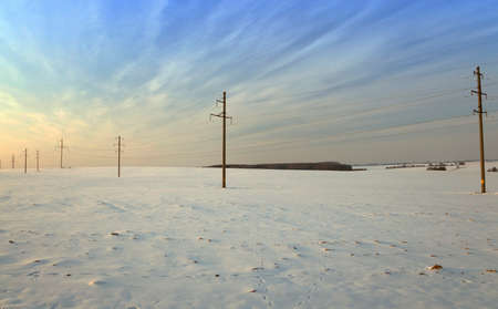 uprise: field covered by snow in winter. on the visible power poles. sunset