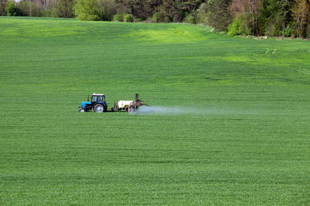 crop sprayer: tractor, photographed in the agricultural field during the processing of Pesticides