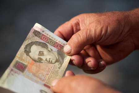 hryvna: photographed close-up of one hundred Ukrainian hryvnia in the hands of the old man, small depth of field Stock Photo