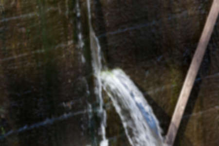 regulate: photographed close-up of the old wooden dam, which formed holes flowing dam defocus Stock Photo