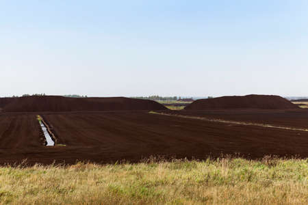 peaty: an area in which production is carried black peat, peat mountains Stock Photo